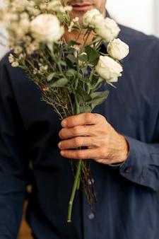 Maschio fiorista in possesso di un bellissimo mazzo di fiori