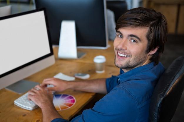 Maschio graphic designer alla scrivania