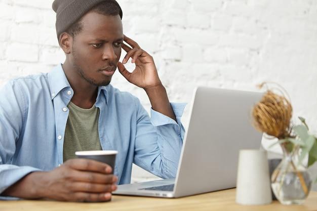 Maschio impegnato con pelle scura che guarda seriamente nel computer portatile mentre legge notizie online, mantenendo la tazza di carta con il caffè, riposando nella caffetteria. libro elettronico di lettura maschio bello sul computer