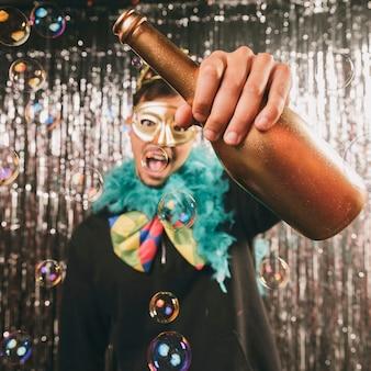 Maschio in costume con bottiglia di champagne