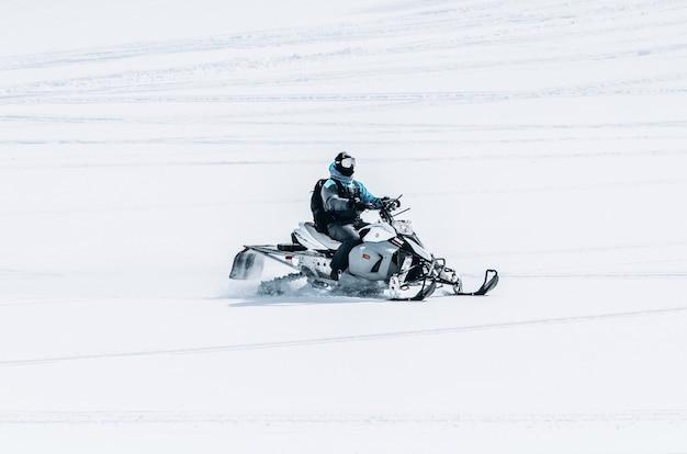Maschio in sella a una motoslitta in un grande campo nevoso