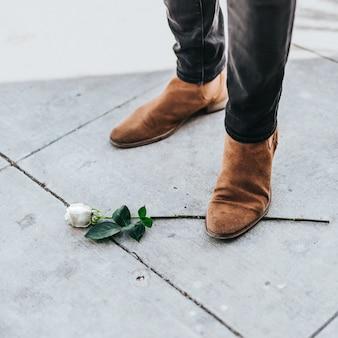 Maschio in stivali da cowboy in piedi su un unico ramo di rosa bianca