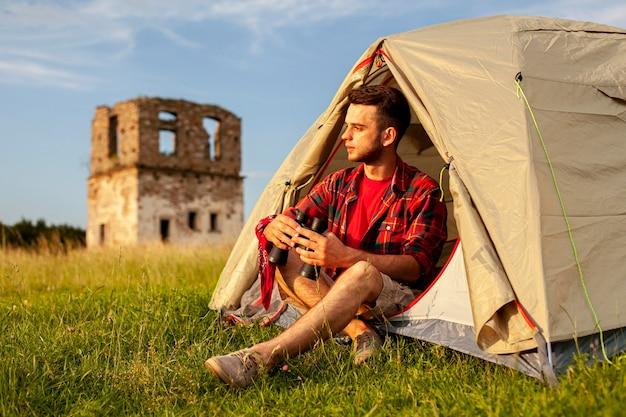 Maschio in tenda da campeggio con binocolo