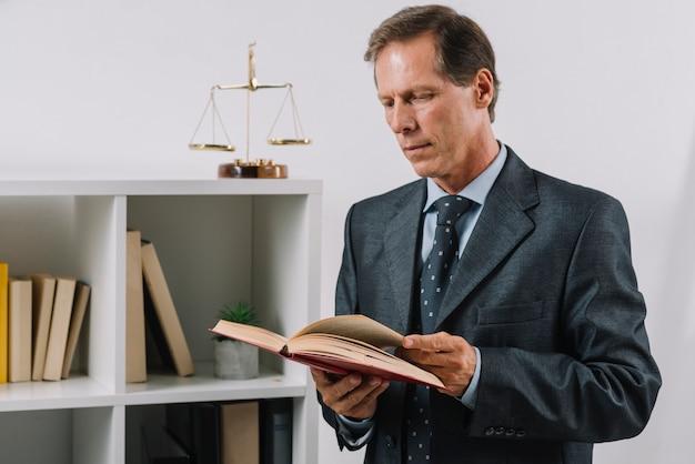 Maschio maturo che legge libro legale nell'aula di tribunale