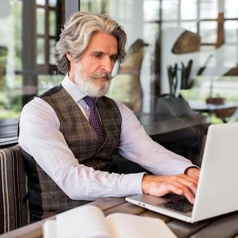 Maschio maturo elegante che lavora al computer portatile