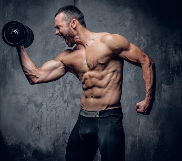 Maschio muscolare che fa gli allenamenti del bicipite