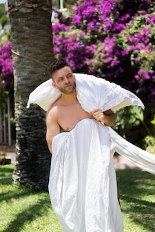 Maschio nudo rilassante in un'amaca in giardino.