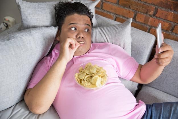 Maschio pigro che mangia pasto mentre per mezzo del telefono cellulare
