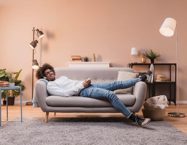 Maschio sdraiato sul divano a giocare
