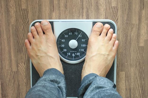 Maschio sulla scala del peso per controllare il peso, concetto di dieta