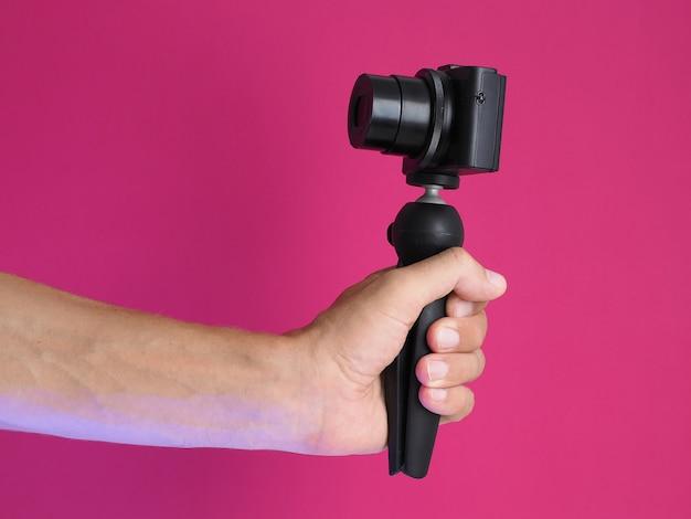Maschio tenendo in mano la fotocamera compatta, realizzando video blog. avvicinamento.