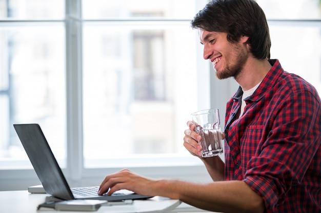 Maschio uomo d'affari con un bicchiere d'acqua, mentre con laptop
