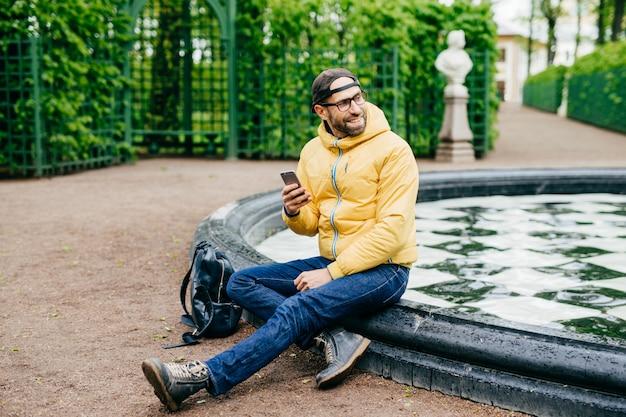 Maschio viaggiatore spensierato rilassato con barba in berretto alla moda, giacca a vento, jeans e occhiali con escursione