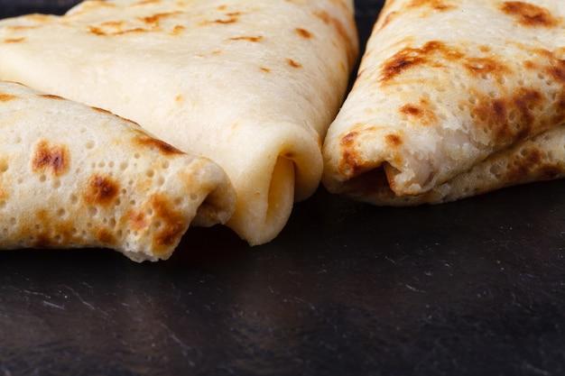 Maslenitsa russo, shrovetide, settimana del pancake, carnevale, shrove, giorno del pancake. una pila di frittelle con burro al piano di sopra sul piatto, sulla superficie di legno, primo piano