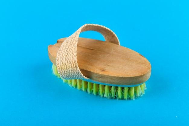 Massaggiatore a pennello in legno. massaggiare la spazzola morbida in legno per il corpo con pelo naturale, indossata sulla mano, su uno sfondo blu, utilizzata in