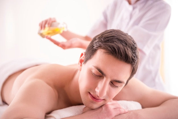 Massaggiatore che fa massaggio sul corpo dell'uomo con olio termale.