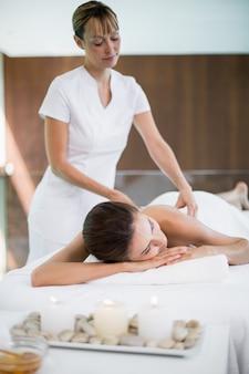 Massaggiatore che massaggia la schiena della donna