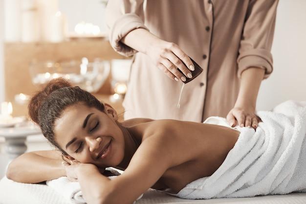 Massaggiatore che versa olio facendo massaggio per la bella donna africana nel salone spa.