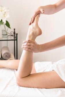 Massaggiatore del primo piano che massaggia piede