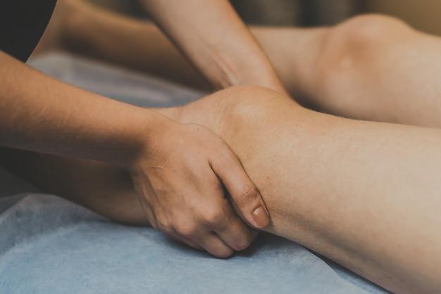 Massaggiatore facendo massaggiare il ginocchio al giovane. il medico massaggia la gamba per il trattamento