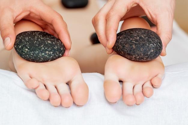 Massaggiatore facendo massaggio ai piedi con pietre.