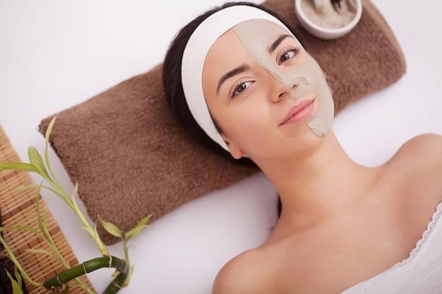 Massaggiatore facendo massaggio alla testa di una donna asiatica nel salone spa