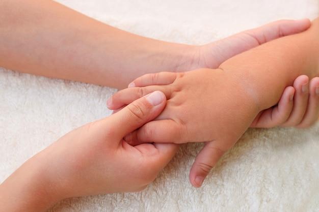 Massaggiatore facendo massaggio dita piccolo bambino.