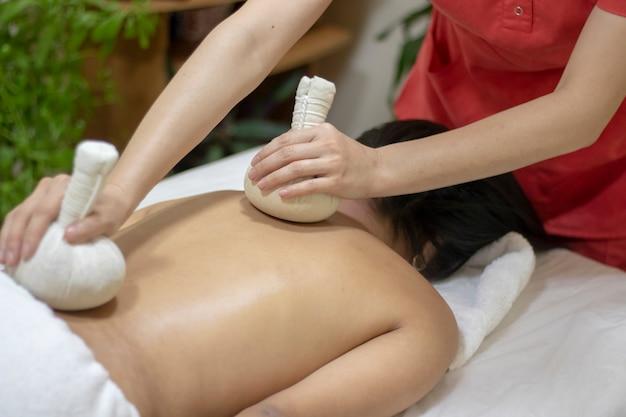 Massaggiatore facendo massaggio sul corpo della donna nel salone spa