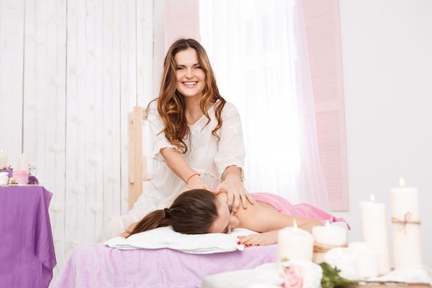 Massaggiatore femminile che fa massaggio sulla parte posteriore della donna sulla stazione termale