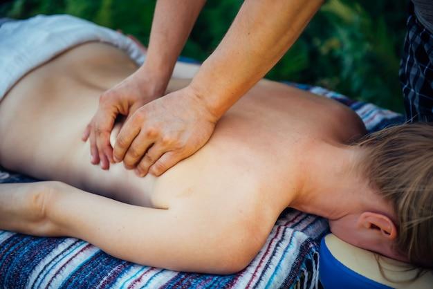 Massaggiatore mani sul retro del paziente in primo piano. donna sui trattamenti di massaggio presso la spa all'aperto. donna rilassata che riceve massaggio benessere. terapia manuale, ripristino della salute della schiena e della colonna vertebrale.