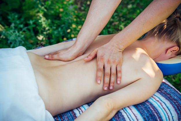 Massaggiatore mani sul retro di un irriconoscibile paziente in primo piano. la donna rilassata riceve un massaggio benessere presso il centro benessere all'aperto