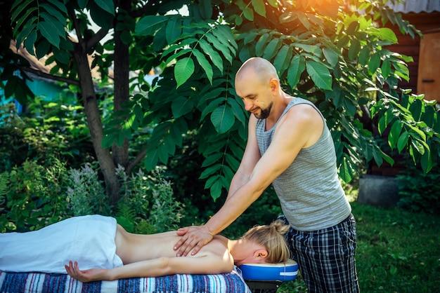 Massaggiatore maschio che dà benessere massaggio alla schiena all'aperto. donna caucasica sdraiata sul lettino da massaggio nel giardino verde del centro benessere. giovane donna in buona salute che gode del massaggio rilassante del corpo