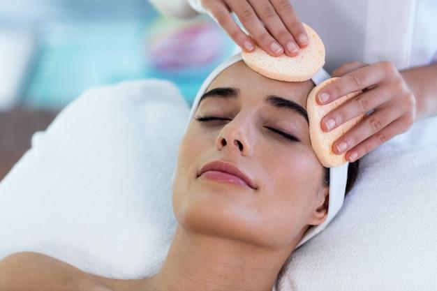 Massaggiatrice donna pulizia viso con tamponi di cotone