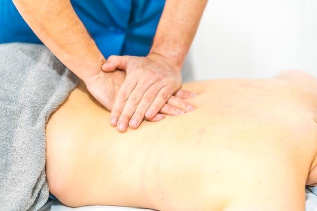 Massaggio con due mani sui reni a un giovane paziente disteso sul suo stomaco. misure di sicurezza per fisioterapia nella pandemia di covid-19. osteopatia, chiromassaggio terapeutico