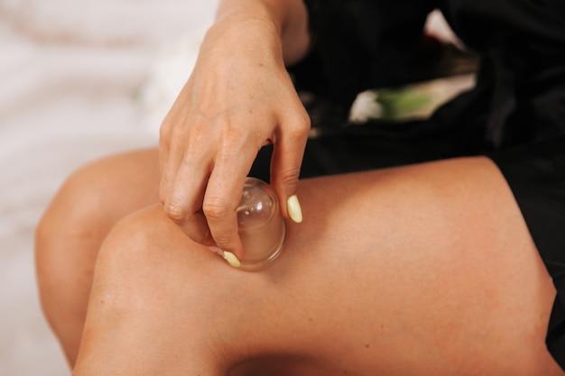 Massaggio con le banche del vuoto a casa sulle cosce