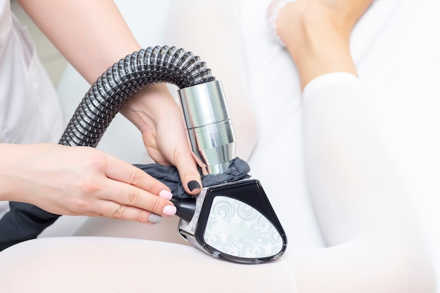 Massaggio corpo ragazza gpl nella spa. la ragazza riceve un massaggio hardware, indossa una tuta speciale per il massaggio.
