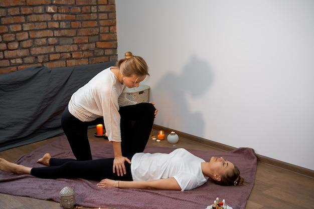 Massaggio curativo tradizionale tailandese. massaggiatore donna caucasica