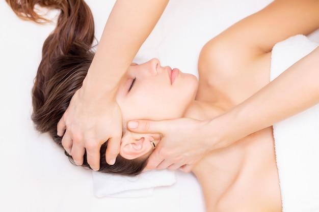 Massaggio e allungamento dei muscoli cervicali. bella ragazza ottiene massaggio in un salone spa