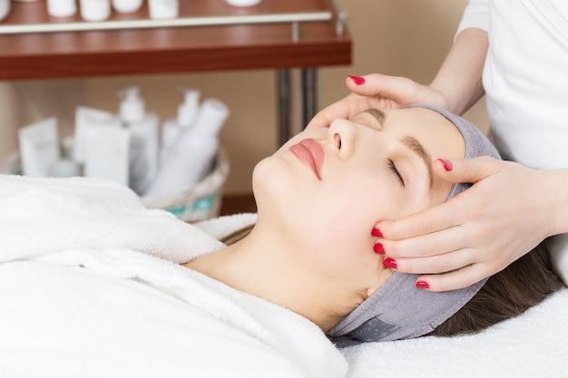 Massaggio facciale per una bella ragazza in un salone spa