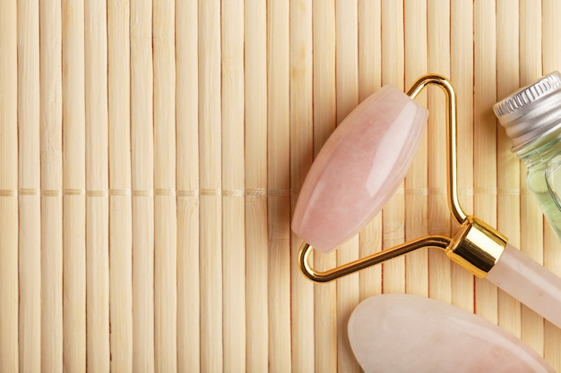 Massaggio gua sha realizzato con rullo di quarzo rosa naturale, pietra di giada e olio, su uno sfondo di bambù per la cura di viso e corpo.
