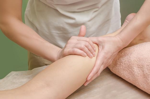 Massaggio professionale rilassante sulla gamba femminile (polpaccio) nel salone.