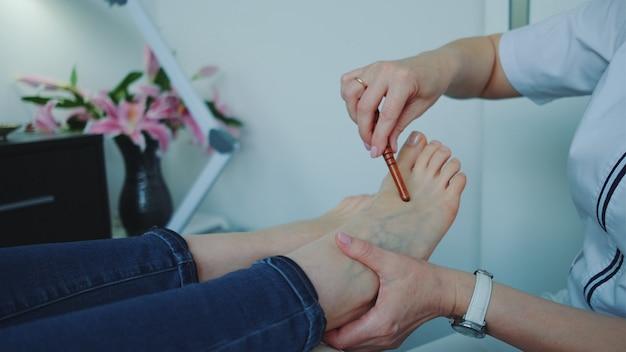 Massaggio shiatsu ai piedi con una bacchetta nel salone di bellezza.