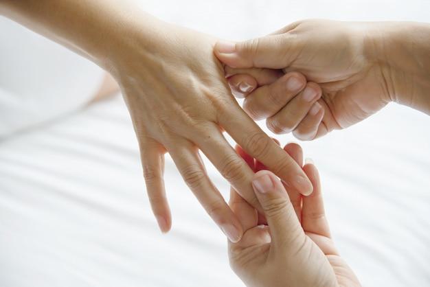 Massaggio termale delle mani sopra un letto bianco pulito