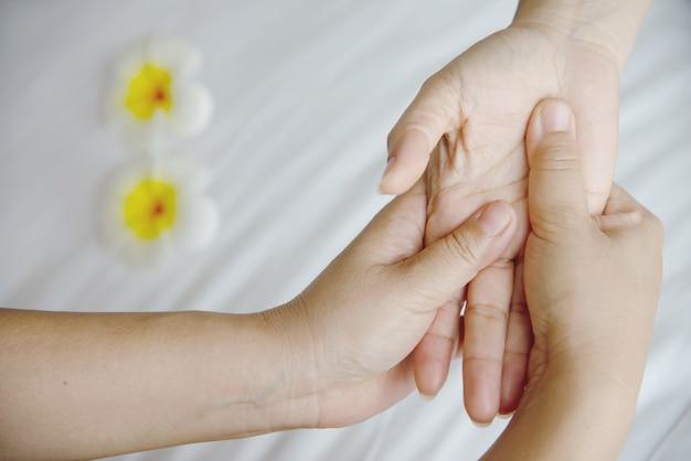 Massaggio termale delle mani su un letto bianco pulito - le persone si rilassano con il servizio di massaggi manuali