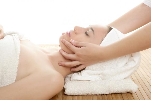 Massaggio viso bella donna con asciugamano bianco
