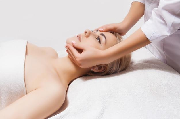 Massaggio viso. primo piano di una giovane donna che riceve il massaggio spa in un salone di bellezza e spa da estetista. spa cura della pelle e del corpo. cura del viso di bellezza. cosmetologia.