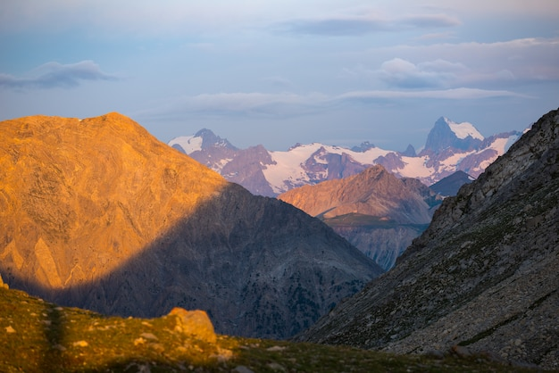 Massif des ecrins france. cielo colorato all'alba, maestose vette e ghiacciai, paesaggio drammatico.