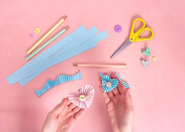Master class di scrapbooking. fai da te. crea una cartolina di san valentino con cuori di carta. hobby delle donne forniture artigianali sul tavolo.