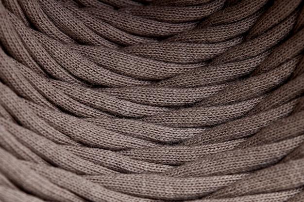 Matassa di primo piano grigio filato lavorato a maglia. tessuto di fibra della fibra del tessuto di modello di struttura del fondo di macrofotografia. strisce di tessuto sono intrecciate su una bobina.