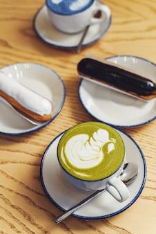 Matcha blu e verde in bicchieri su un tavolo di legno in una caffetteria accanto a un dolce dessert. bignè con ganache al cioccolato e glassa con diversi condimenti